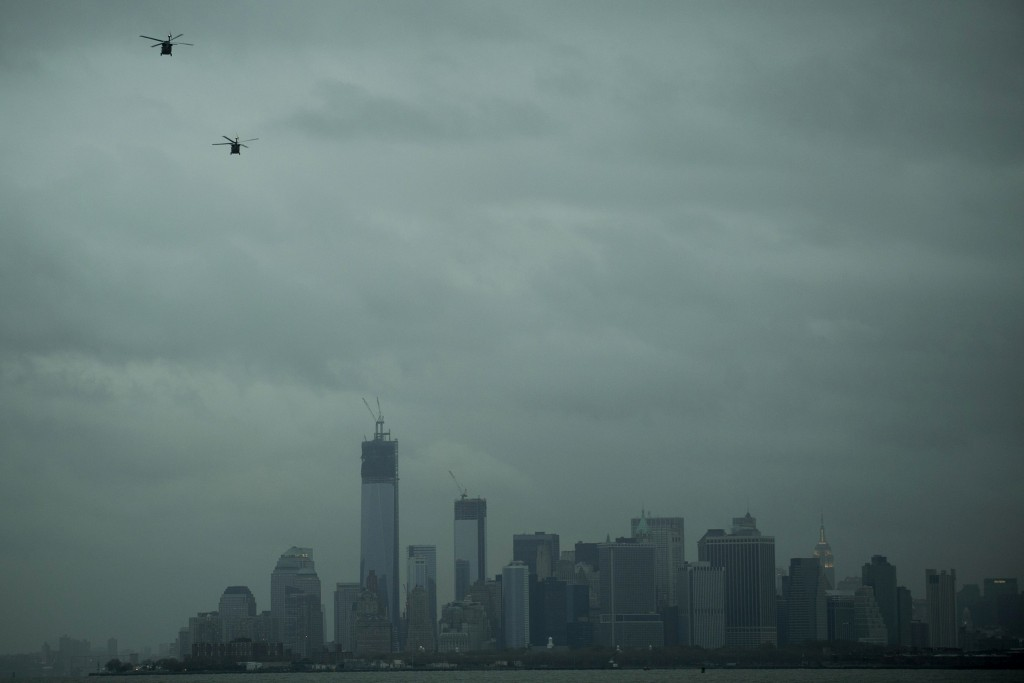 Helicopters fly over the skyline of lower Manhattan as it sits in darkness after a preventive power outage caused by Hurricane Sandy in New York October 30, 2012. Hurricane Sandy began battered the U.S. East Coast on Monday with fierce winds and driving rain, as the monster storm shut down transportation, shuttered businesses and left hundreds of thousands without power. REUTERS/Keith Bedford (UNITED STATES - Tags: SOCIETY ENVIRONMENT CITYSPACE)